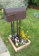mailbox in area of flowers bounded by bricks